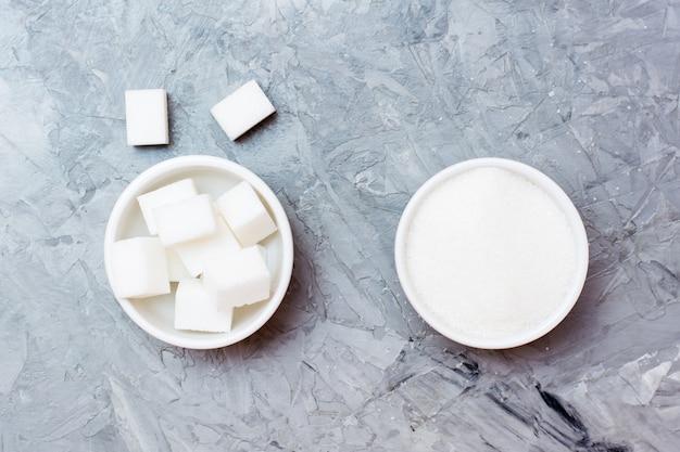 シュガーキューブとテーブルの上の白いボウルのグラニュー糖