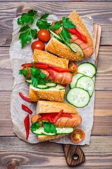 ごまパンと木製のテーブルの上の皿に新鮮な野菜のホットドッグ