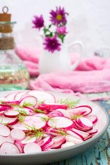 大根とディルの木製テーブルの上の皿の部分の新鮮なサラダ