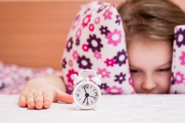 白い目覚まし時計が目を覚ます少女のテーブルの上に立つ