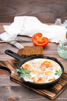 木製テーブルの上のまな板の上の鍋にトマトとハーブのシャクシュカ炒め卵の自家製朝食