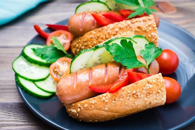 Готовые к употреблению хот-доги из жареных колбас, кунжутные булочки и свежие овощи на тарелку на деревянном столе. крупный план