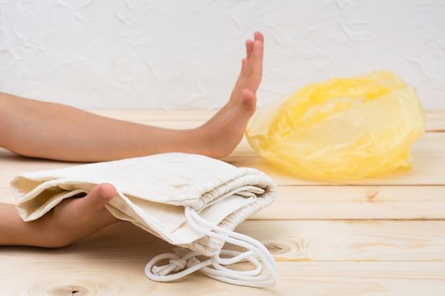 手は、木製のテーブルの上にビニール袋ではなく、キャンバスの買い物袋の選択を示しています。廃棄物ゼロ。