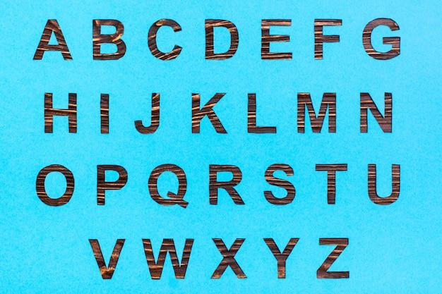 英語のアルファベットの文字は青い段ボールから刻まれており、隙間には木製のものが見えます