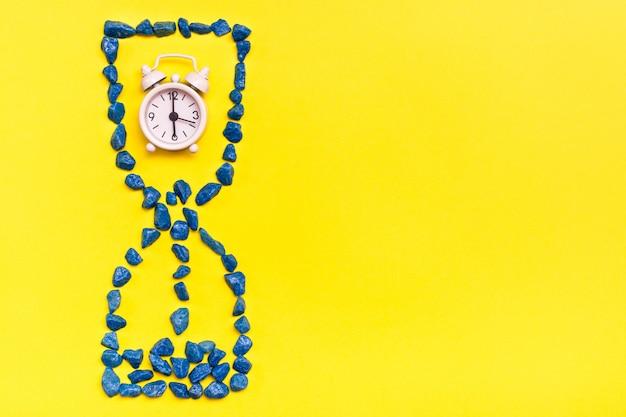 黄色の背景に装飾的な石で作られた砂時計の中の目覚まし時計。漏れ時間の概念