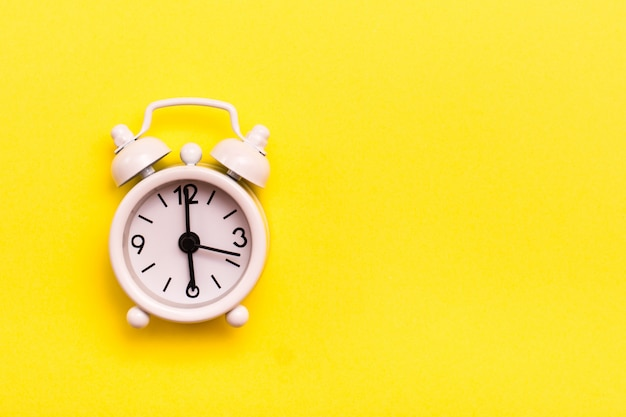 黄色の背景に白の古典的な目覚まし時計