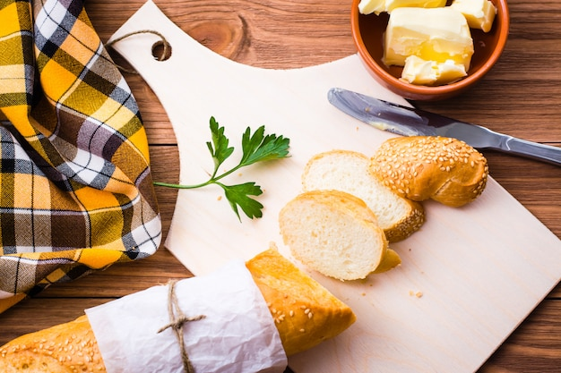 まな板の上のバゲット、バター、パセリのスライス。上面図