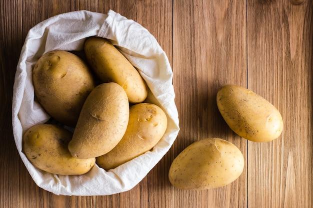 Сырой неочищенный картофель в сумке и на деревянном столе. вид сверху