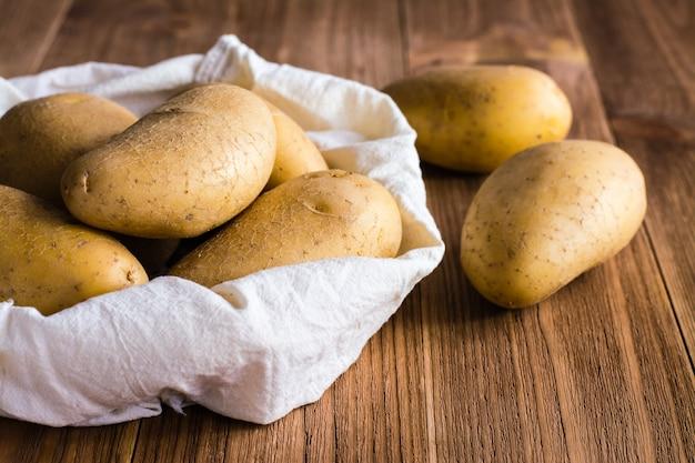 Сырой неочищенный картофель в сумке и на деревянном столе