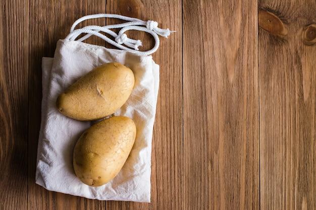 Клубни картофеля лежат на холсте на деревянном столе. вид сверху