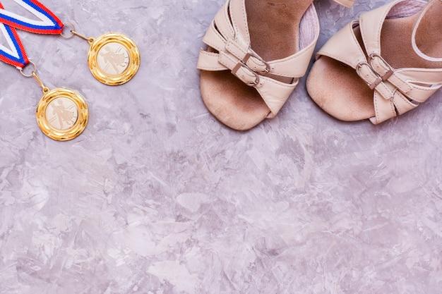 Две медали на ленте и обувь для спортивных бальных танцев, вид сверху