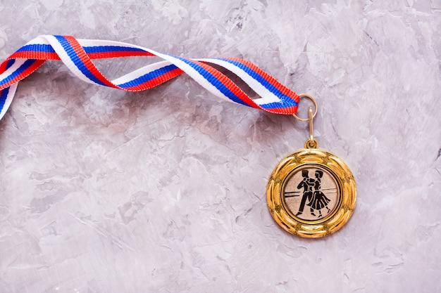 Медаль с изображением танцоров на ленте на сером неоднородном фоне, вид сверху