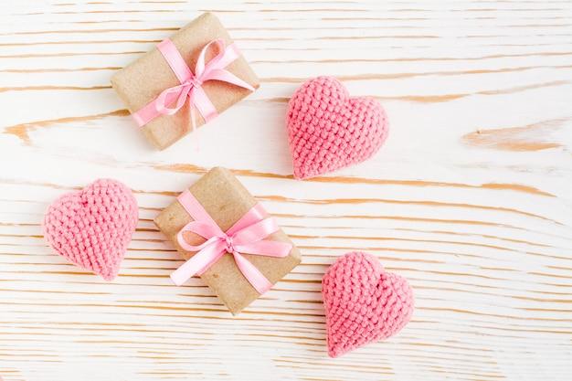 カップルはピンクのリボンで贈り物を包み、白い木の上面にニットの心