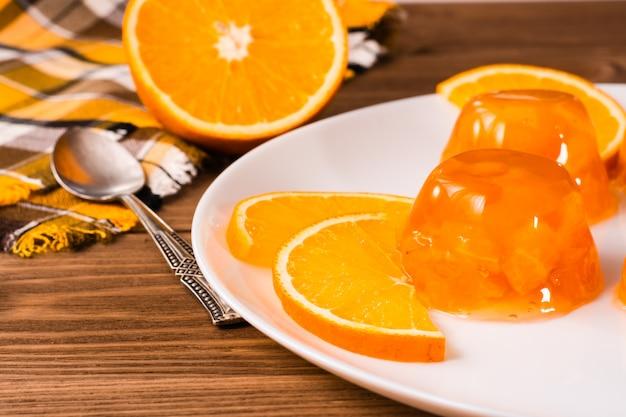 オレンジのゼリーと木製のテーブルの上の皿にオレンジ
