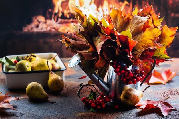 秋の葉と暖炉の近くの熟した梨の水まき缶