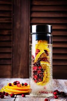 ガラス瓶の中のクランベリーとオレンジを注入した水