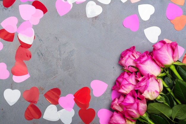 Декоративные сердечки и розовые розы на сером камне