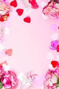 Красивая розовая роза, декоративные сердечки конфетти и розовая лента на розовом