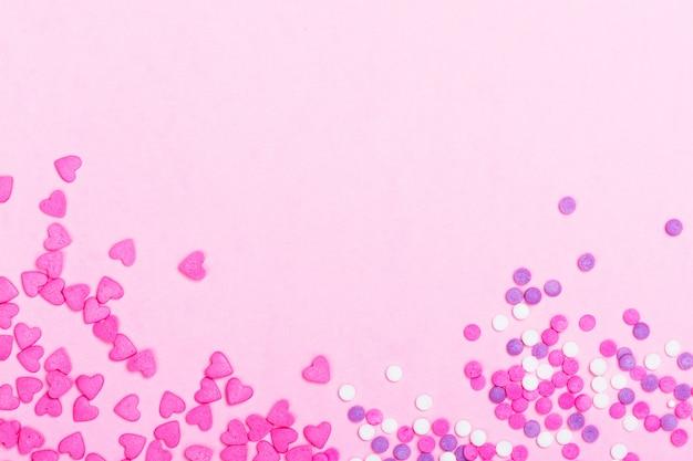 Розовые брызги в форме сердца на розовом