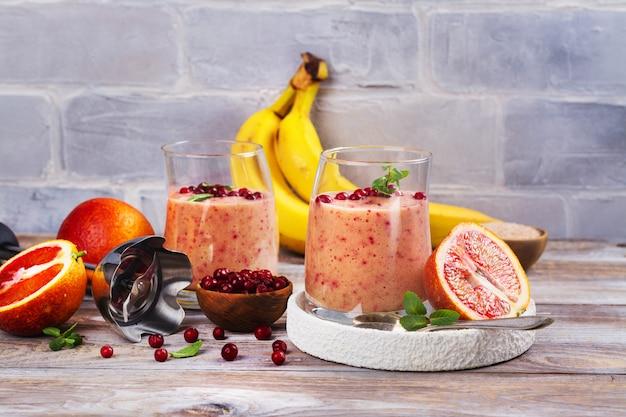 Здоровый освежающий розовый коктейль с яблоком, красными апельсинами, брусникой и отрубями