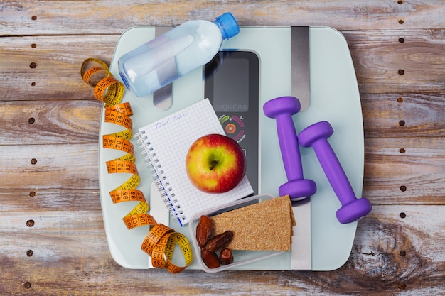体重計、健康的なスナック、ダンベル、測定テープ。