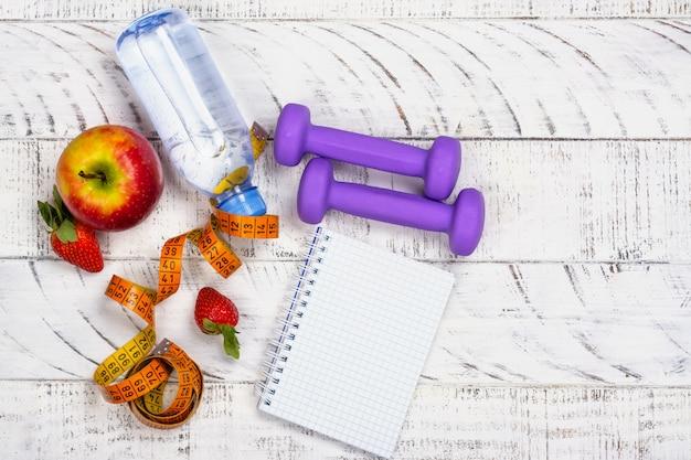 リンゴ、水のボトルと白の測定テープ