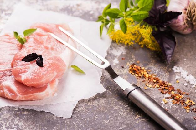 Сырцовые свежие стейки и приправы свинины на предпосылке металла.