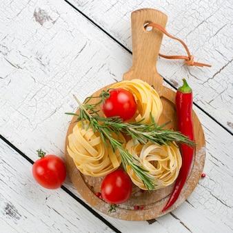 トマト、赤唐辛子、ローズマリーの白い木製のテーブルの上のイタリアンパスタ。