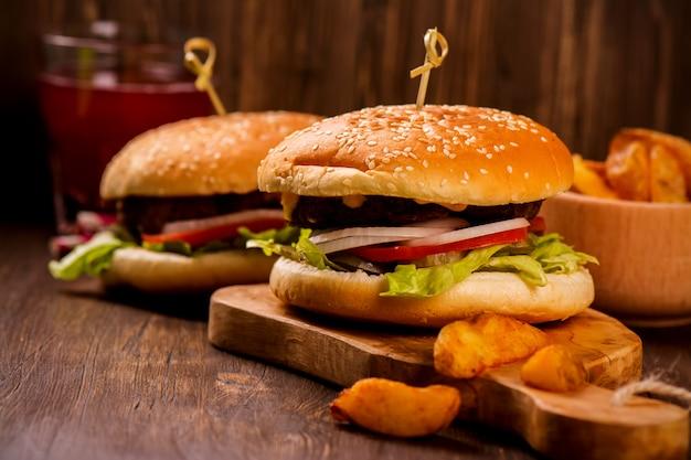 木製の素朴なテーブルの上のフライドポテトとジューシーで香りのよいハンバーガー