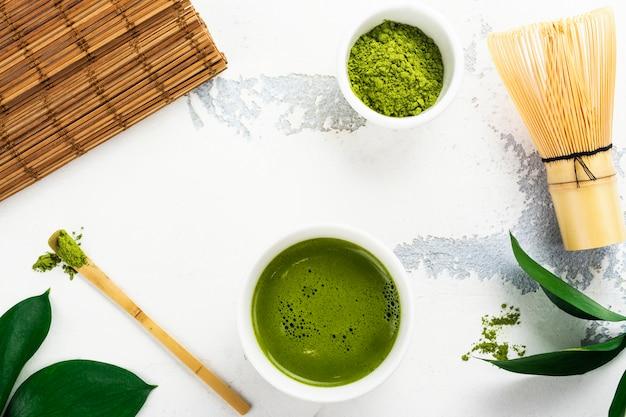 緑の抹茶茶飲料と白い背景の上の茶アクセサリー
