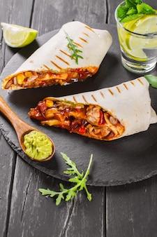 おいしいファーストフード:黒い木製の背景にワカモレソースとメキシコのブリトー