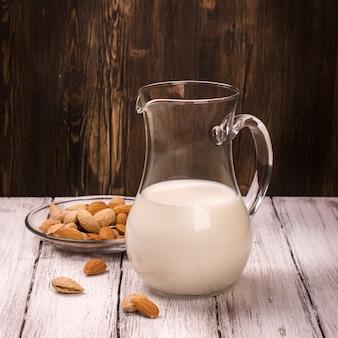 Миндальное молоко в стеклянной банке на деревянных фоне.
