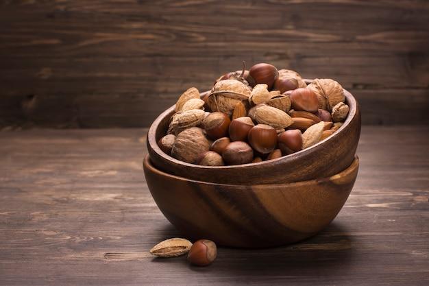 素朴な背景の上の木製ボウルナッツの品揃え