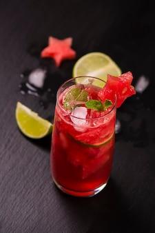 黒い石のテーブルの上のスイカの星によって飾られた高いガラスで新鮮なスイカとライム