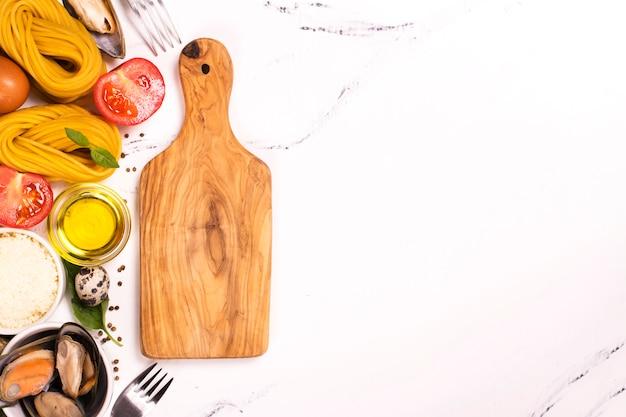 Паста с ингредиентами на белом мраморном столе