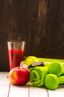 フィットネスやダイエットのコンセプト:ダンベル、新鮮な赤いスムージー、アップル