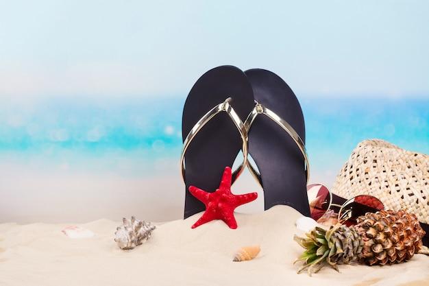 海の近くの美しい砂浜でビーチサンダル、帽子、サングラス。コピースペース