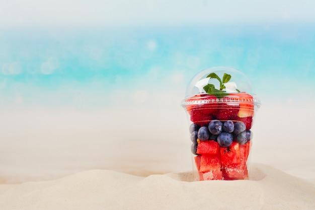 新鮮なカットフルーツとベリーがいっぱい入ったプラスチック製のコップ