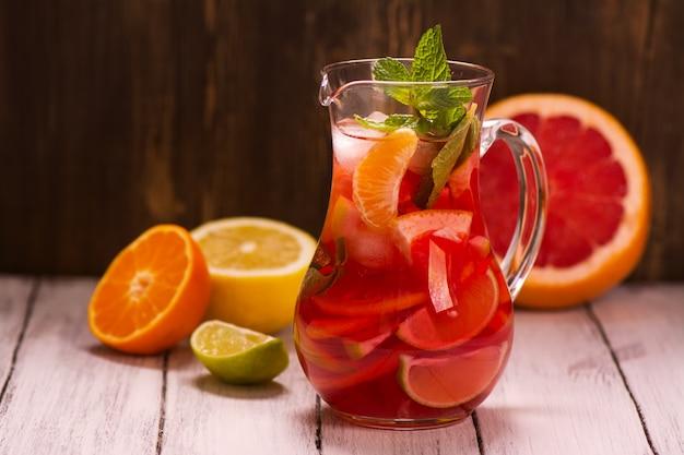 別の柑橘類と伝統的な赤いスペインのサングリアの瓶を飲む
