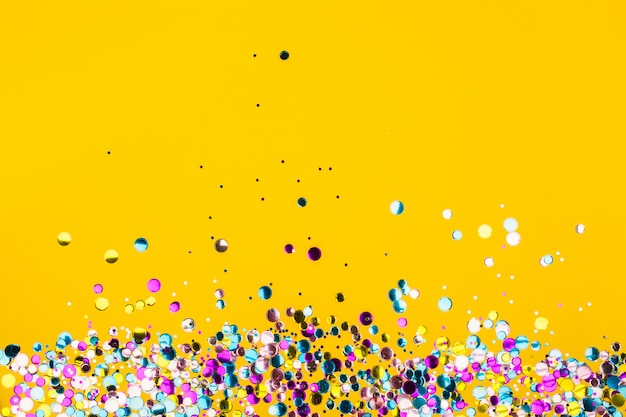 黄色の背景にカラフルな紙吹雪
