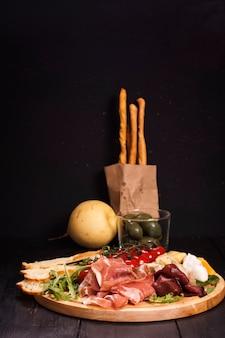 Различные виды итальянских закусок: ветчина, сыр, гриссини, оливки, фрукты