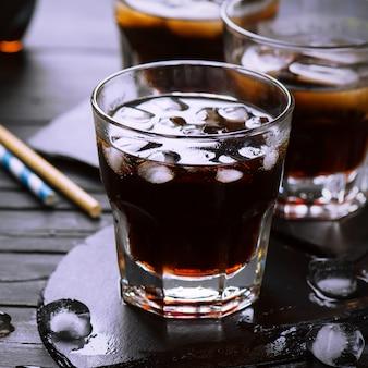 暗い木製のテーブルの上のグラスにアイスキューブとコーラ