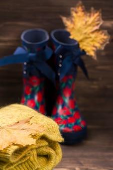 秋の概念:子供の暖かい服装と茶色の木製の背景にゴム長靴。