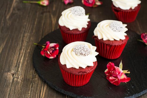木製の背景に赤いベルベットのカップケーキ