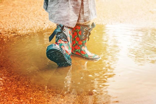 雨のブーツの女の子は水たまりに立っています。