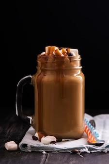 黒の木製テーブルの上のメイソンジャーのキャラメルコーヒー