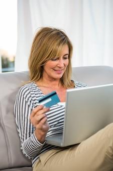 彼女のクレジットカードを使ってインターネットで支払いをする女性