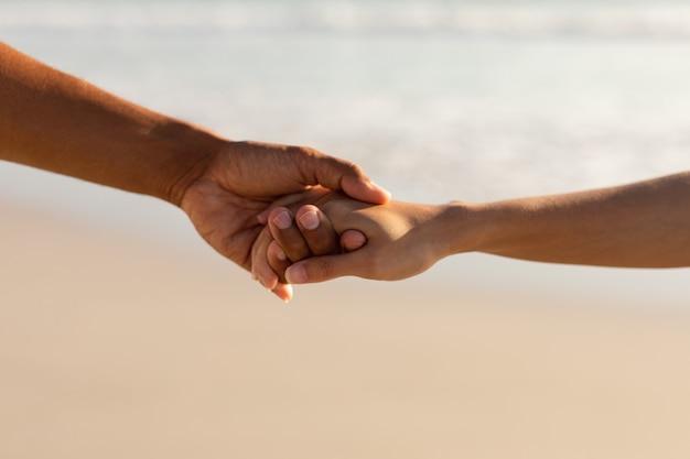 ビーチでお互いの手を繋いでいるカップル