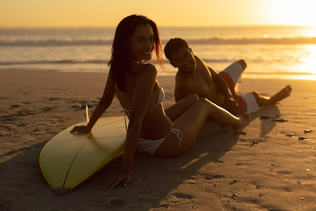 夕暮れ時にビーチでリラックスしたサーフボードをカップルします。
