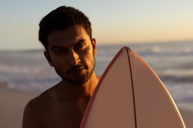 ビーチでサーフボードに立っている男